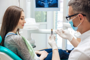 dentist showing female patient a dental implant model