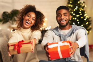 a man and woman smiling and holding presents