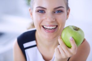 woman holding an apple after visiting her dentist in Beaumont